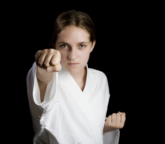 384015-pretty-young-girl-in-a-karate-pose-on-black-background